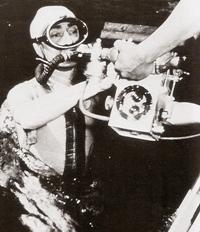 Jacques-Yves Cousteau s'apprête à plonger avec  un appareil photo de prise de vue sous-marine